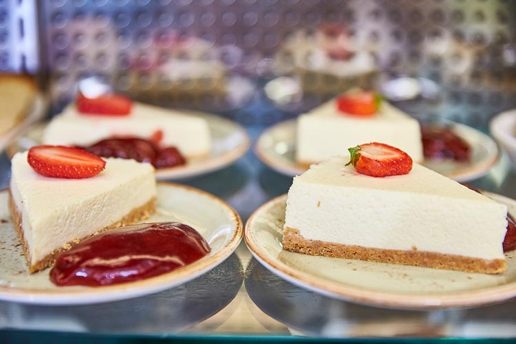Selection of cheesecakes topped with cut strawberries